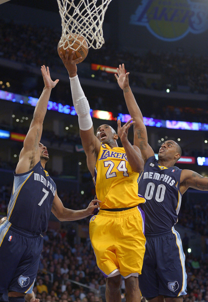 Photo - Los Angeles Lakers guard Kobe Bryant, center puts up a shot as Memphis Grizzlies guard Jerryd Bayless, left, and forward Darrell Arthur defend during the first half of their NBA basketball game, Friday, April 5, 2013, in Los Angeles. (AP Photo/Mark J. Terrill)