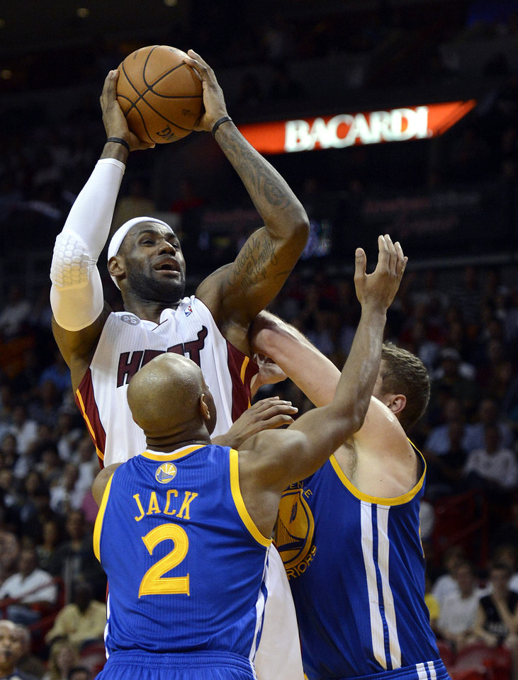 Miami Heat's LeBron James, top, is defended by Golden State Warriors' Jarrett Jack (2) and David Lee, right, during an NBA basketball game on Wednesday, Dec. 12, 2012, in Miami. Lee was called for a flagrant foul on the play. (AP Photo/Rhona Wise)