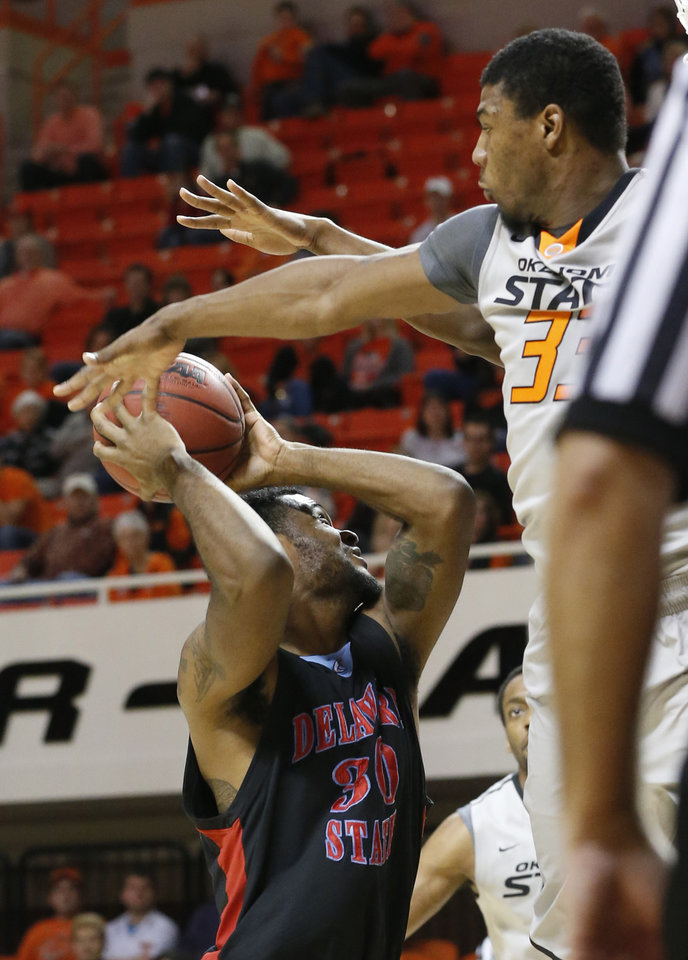 Photo - Oklahoma State guard Marcus Smart, right,  jumps up to attempt to block a shot by Delaware State guard Jordan Lawson, left, in the first half of an NCAA college basketball game in Stillwater, Okla., Tuesday, Dec. 17, 2013. (AP Photo/Sue Ogrocki)