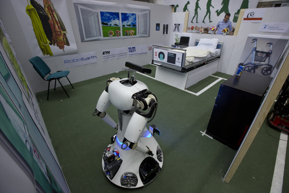 Photo - Amigo, a white robot the size of a person, uses information gathered by other robots to move towards a table to pick up a carton of milk and deliver it to an imaginary patient in a mock hospital room at the Technical University of Eindhoven, Netherlands, Wednesday Jan. 15, 2014. A group of five of Europe's top technical universities, together with technology conglomerate Royal Philips NV, are launching an open-source system dubbed