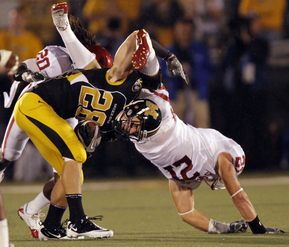 Oklahoma's Tom Wort (21) goes over the top of Missouri's T.J. Moe (28) during the first half of the college football game between the University of Oklahoma Sooners (OU) and the University of Missouri Tigers (MU) on Saturday, Oct. 23, 2010, in Columbia, Mo.  Photo by Chris Landsberger, The Oklahoman