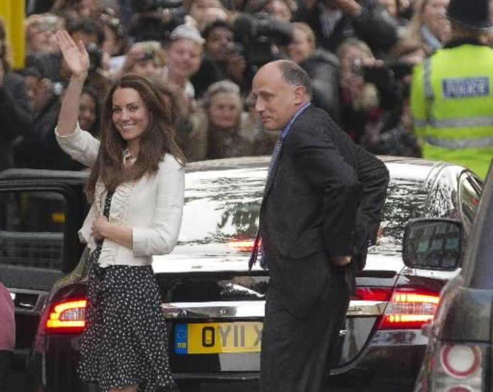 Photo - Kate Middleton, left, gestures to the crowds gathered outside the Goring Hotel in London, Thursday April 28, 2011, ahead of her wedding to Britain's Prince William on Friday April 29. (AP Photo/Joel Ryan)