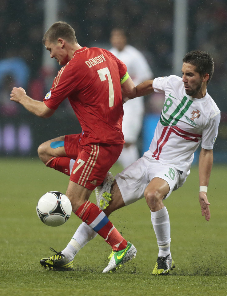 Photo -   Portugal's Joao Moutinho, right, challenges for the ball with Russia's Igor Denisov, left, in their World Cup 2014 Group F qualification match at Luzhniki stadium in Moscow, Russia, on Friday, Oct. 12, 2012. (AP Photo/Mikhail Metzel)