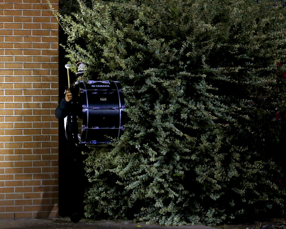 A Putnam City band member walks through a bush on their way to perform during halftime of Putnam City's football game against Sapulpa at Putnam City in Oklahoma City, Thursday, Sept. 26, 2013. Photo by Bryan Terry, The Oklahoman