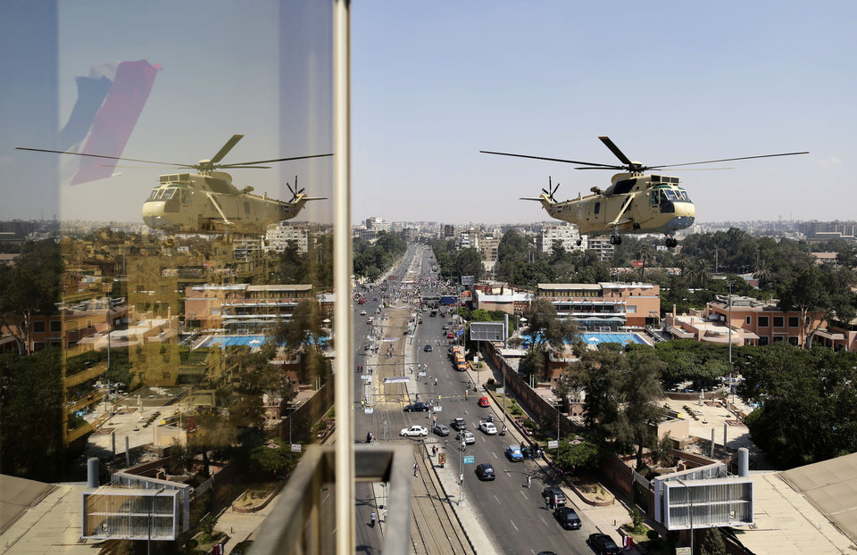 Photo - An Egyptian military helicopter reflects on a glass window as it flies over the presidential palace in Cairo, Egypt, Friday, July 26, 2013. Political allies of Egypt's military lined up behind its call for huge rallies Friday to show support for the country's top general, Abdel-Fattah el-Sissi, pushing toward a collision with Islamist opponents who are also calling for rallies demanding the return of Mohammed Morsi, the nation's ousted president. (AP Photo/Hassan Ammar)