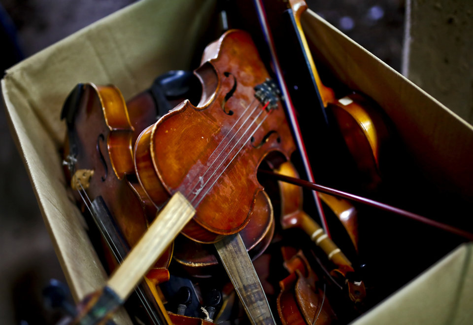 Photo - A box of broken beyond repair violins that violinist Kyle Dillingham use to create music while performing in Oklahoma City, Okla. on Tuesday, Nov. 19, 2013. Dillingham uses the broken violins as a representation that no mater how broken people may think they are, they are still able to create music in life. Photo by Chris Landsberger, The Oklahoman