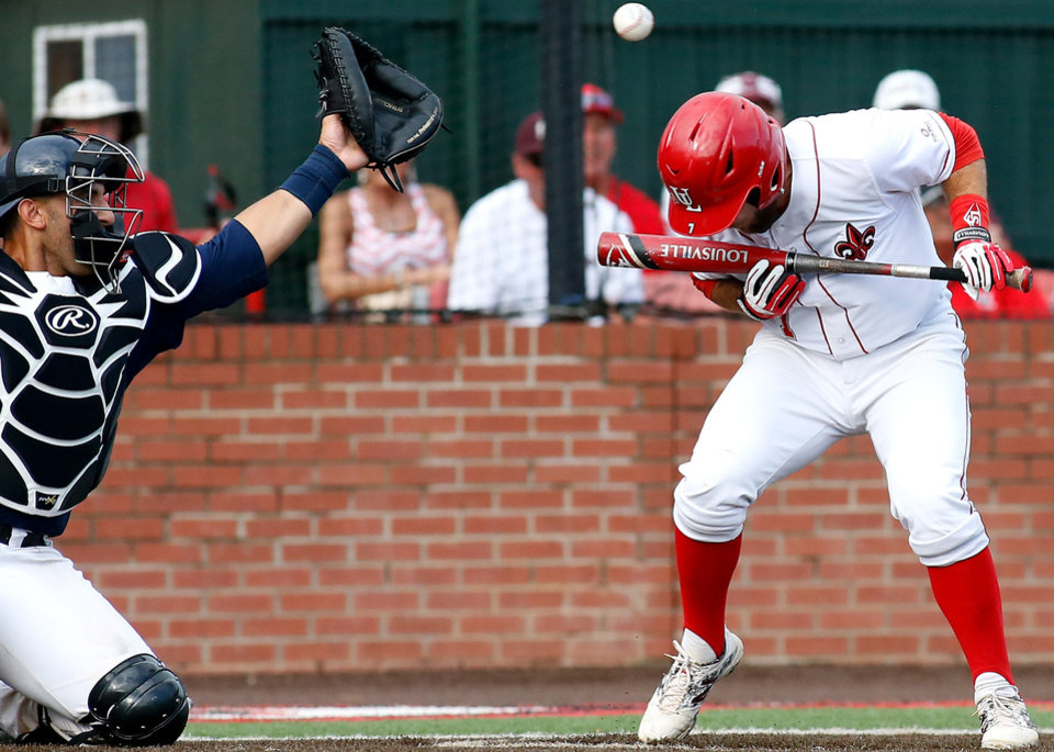 Photo - Louisiana-Lafayette's Ryan Leonards, right, ducks under a wild pitch from Jackson State pitcher Jamal Wilson in the seventh inning during an NCAA college baseball tournament regional game in Lafayette, La., Sunday, June 1, 2014. Louisiana-Lafayette won 11-1. (AP Photo/Jonathan Bachman)