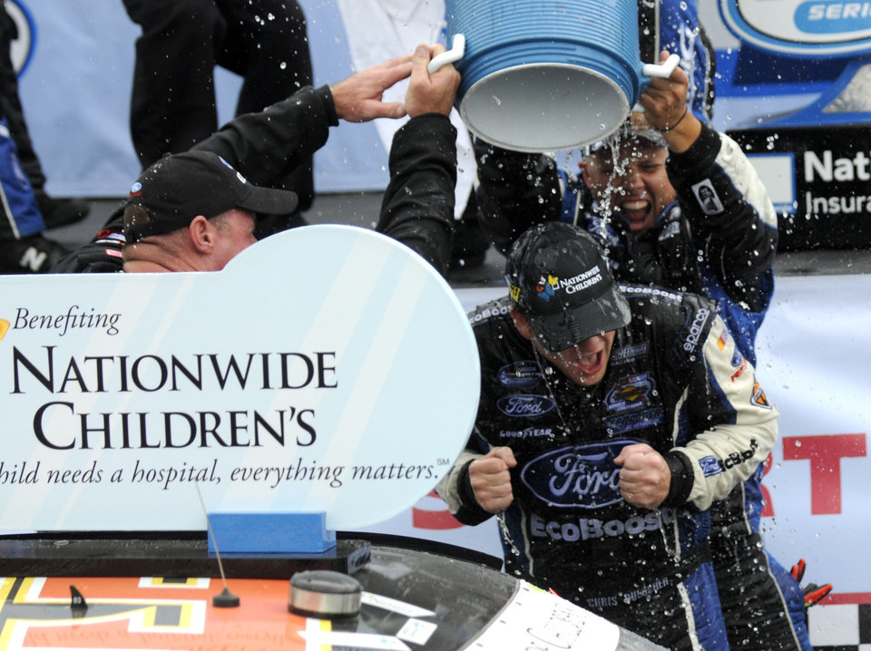 Photo - Chris Buescher is doused by his crew after winning the NASCAR Nationwide Series Nationwide Children's Hospital 200 auto race at Mid-Ohio Sports Car Course Saturday, Aug. 16, 2014, in Lexington, Ohio. (AP Photo/Tom E. Puskar)