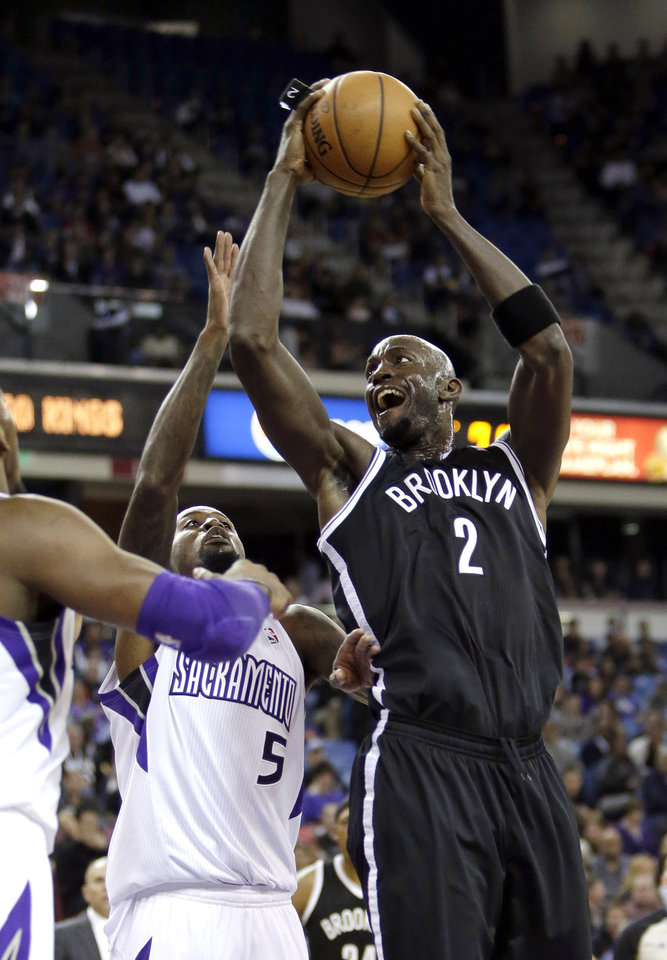 Photo - Brooklyn Nets forward Kevin Garnett, right, goes to the basket against Sacramento Kings forward John Salmons, during the first quarter of an NBA basketball game in Sacramento, Calif., Wednesday, Nov. 13, 2013. (AP Photo/Rich Pedroncelli)