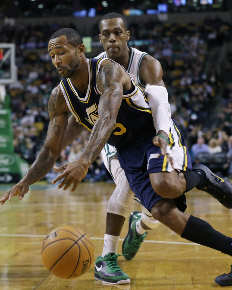 Boston Celtics point guard Rajon Rondo, right, reaches around Utah Jazz point guard Mo Williams (5) while trying to defend against Williams' drive to the hoop during the first half of an NBA basketball game in Boston, Wednesday, Nov. 14, 2012. (AP Photo/Elise Amendola)