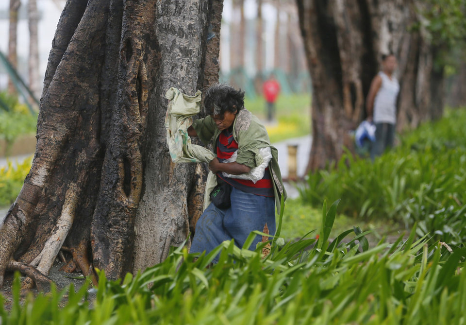 Photo - A woman seeks shelter behind a tree as strong winds and slight rain brought by Typhoon Koppu hit Manila, Philippines Sunday, Oct. 18, 2015. The slow-moving typhoon blew ashore with fierce wind in the northeastern Philippines early Sunday, toppling trees and knocking out power and communications. Officials said there were no immediate reports of casualties. (AP Photo/Bullit Marquez)