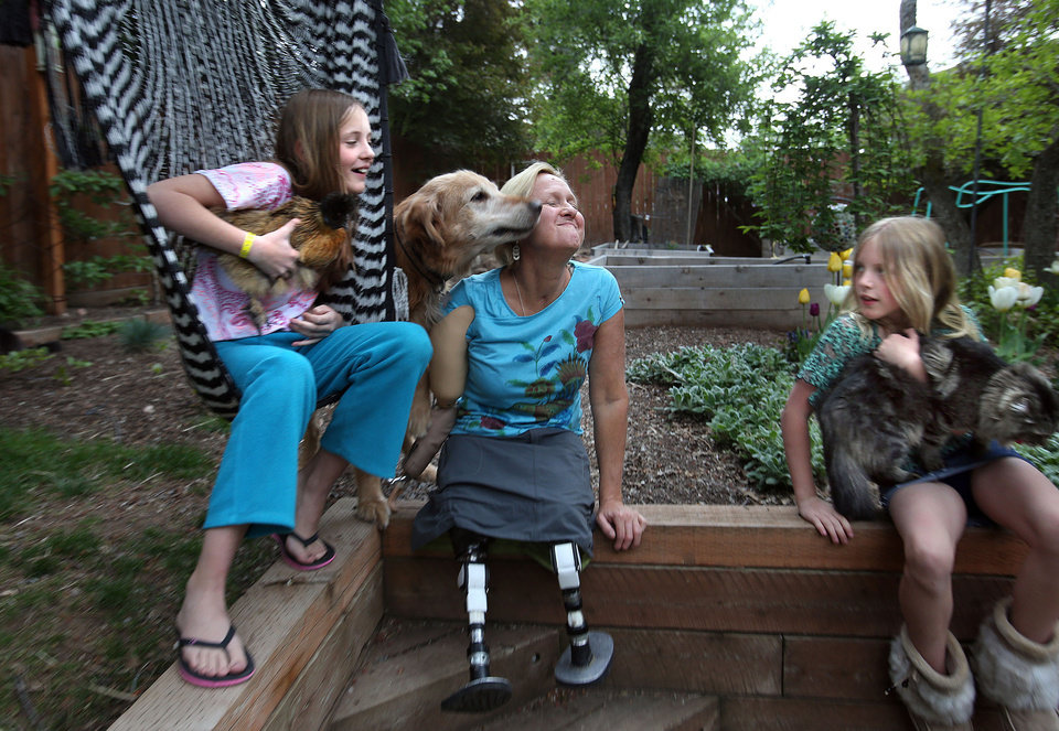 Photo -       Lisa Speckman gets a kiss from her dog, Rascal, while sitting with her daughters, Hannah, 11, and Lily, 9, in Salt Lake City on Monday, May 5, 2014.