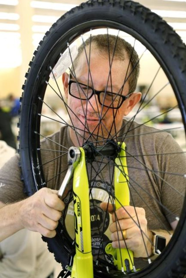Photo -  Greg Hincke, member of the Oklahoma Bicycle Society, tightens a bolt while attaching a wheel to the bicycle frame during the 2018