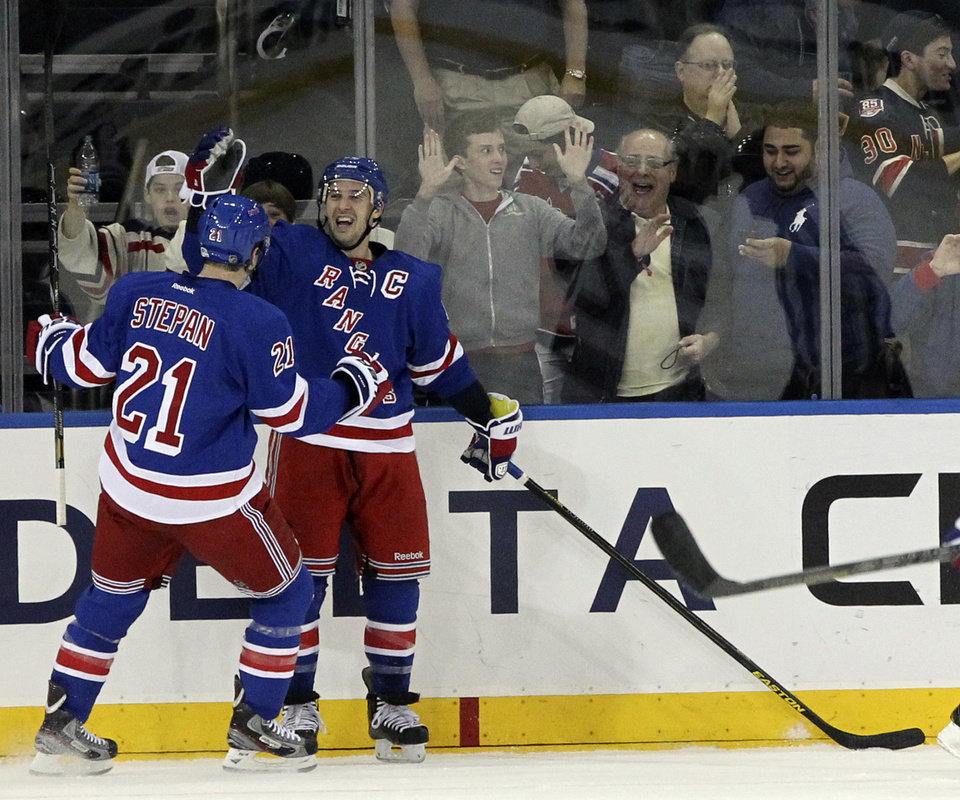 Photo - New York Rangers' Ryan Callahan, right, celebrates with Derek Stepan (21) after scoring a goal during the first period of an NHL hockey game against the New Jersey Devils, Saturday, April 27, 2013 at Madison Square Garden in New York.  (AP Photo/Mary Altaffer)