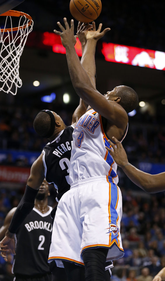 Photo - Thunder's Serge Ibaka (9) rebounds over Brooklyn's Paul Pierce (34) in the second half of an NBA basketball game where the Oklahoma City Thunder were defeated 95-93 by the Brooklyn Nets at the Chesapeake Energy Arena in Oklahoma City, on Thursday, Jan. 2, 2014. Photo by Steve Sisney, The Oklahoman