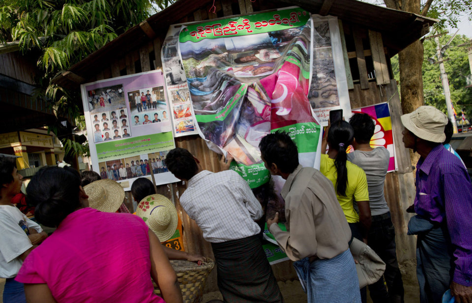 Photo - In this March 28, 2013 photo, visitors to the Ma Soe Yein monastery gather to look at posters displaying the