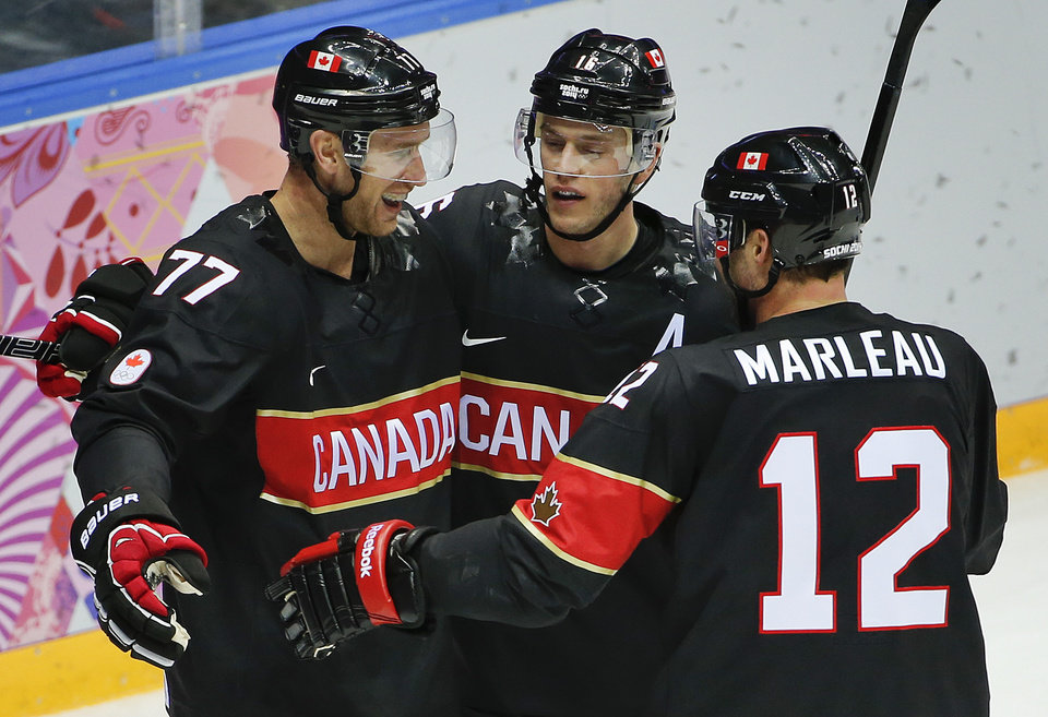 Photo - Canada forward Jeff Carter, left, is congratulated by forward Jonathan Toews and forward Patrick Marleau after scoring his second goal of the second period during a men's ice hockey game against Austria at the 2014 Winter Olympics, Friday, Feb. 14, 2014, in Sochi, Russia. (AP Photo/Julio Cortez)