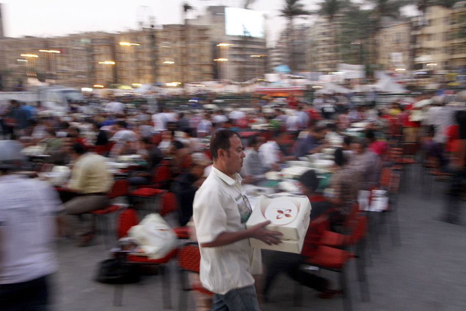 Photo - Egyptians break their fast the first day of Ramadan outside Tahrir Square in Cairo, Egypt, Wednesday, July 10, 2013. Egyptians break their fast during the first day of Ramadan outside Tahrir Square in Cairo, Egypt, Wednesday, July 10, 2013. After a week of violence and mass demonstrations, Egyptians were hoping that Wednesday's start of the Muslim holy month of Ramadan will significantly calm the streets. The sunrise-to-sunset fast cuts down on daytime activity, although there are fears of unrest at night.(AP Photo/Nasser Shiyoukhi)