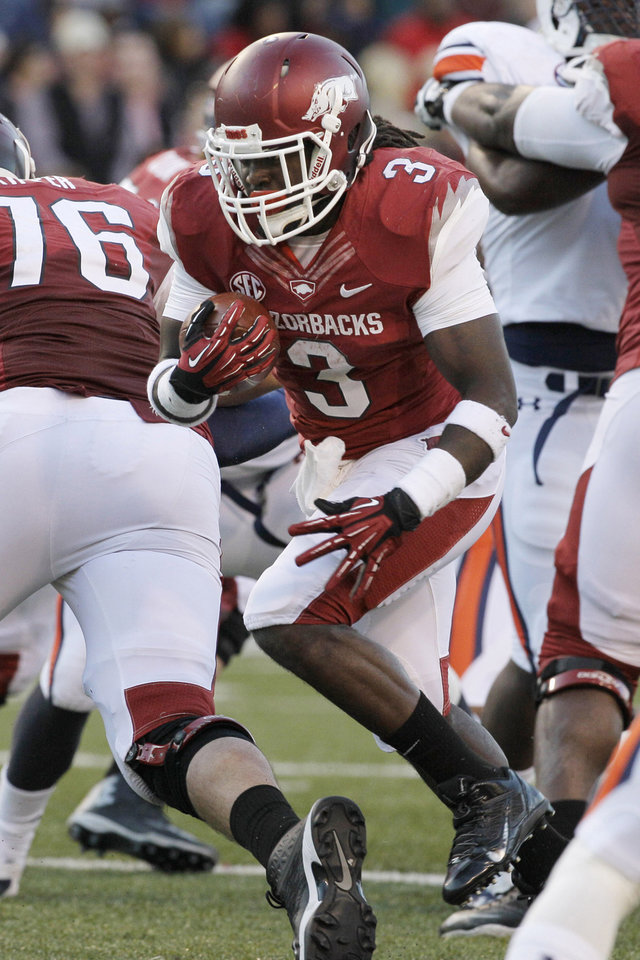 Photo - FILE - In this Nov. 2, 2013, file photo, Arkansas running back Alex Collins (3) carries against Auburn during the first half of an NCAA college football game in Fayetteville, Ark. Collins will return for the 2014 season. (AP Photo/Danny Johnston, File)