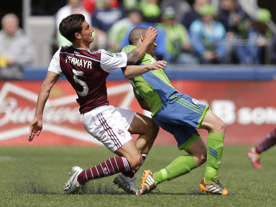 Photo - Seattle Sounders' Osvaldo Alonso, right is fouled by Colorado Rapids' Thomas Piermayr, left, Saturday, April 26, 2014, in the first half of an MLS soccer match in Seattle. Piermayr was given a yellow card on the play. (AP Photo/Ted S. Warren)