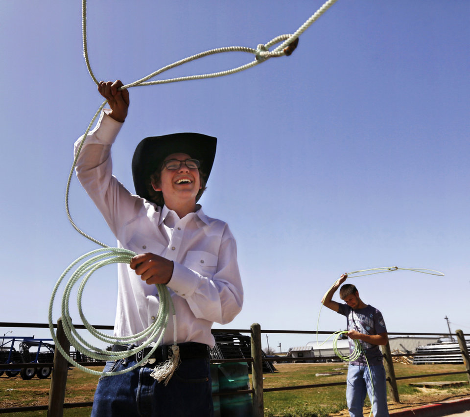 Photo - Team ropers Cole Campbell of Pauls Valley, foreground, and his pal, Curt Richardson of Elmore City, get in some roping practice on a roping dummy during off-time while they're not showing their animals at the Oklahoma Youth Expo at State Fair Park on Tuesday,   March 18, 2014.  Photo by Jim Beckel, The Oklahoman