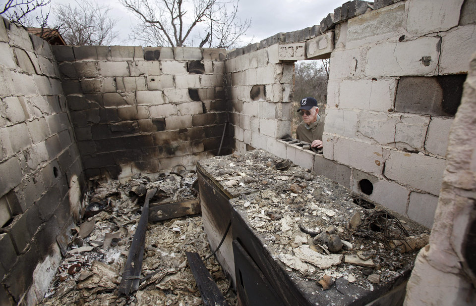 Photo - Tex Cyr looks through the window of his destoyed home as he surveys the damage caused by wildfires on Friday, April 10, 2009, in Choctaw, Okla.  Photo by Chris Landsberger, The Oklahoman