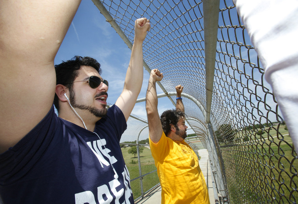 Photo - Fredy Valencia and Amir Darvishzadeh hold their hand up in a fist to show solidarity while protesting on the walk bridge over Interstate 44 in Woodson Park. The rally was a part of a national campaign to raise awarness about the Dream Act.  David McDaniel - The Oklahoman