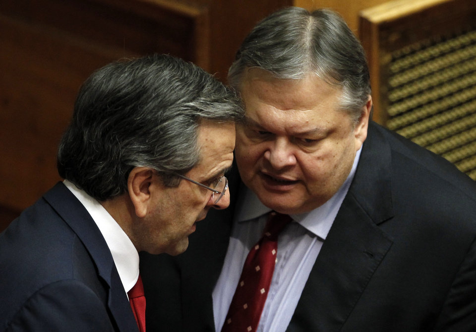 Photo -   Greek Prime Minister Antonis Samaras, left, speaks with Socialist Leader Evangelos Venizelos at the Parliament during a debate on the new government's policy agenda before staging a vote of confidence in Athens, late Sunday July 8, 2012. (AP Photo/Kostas Tsironis)