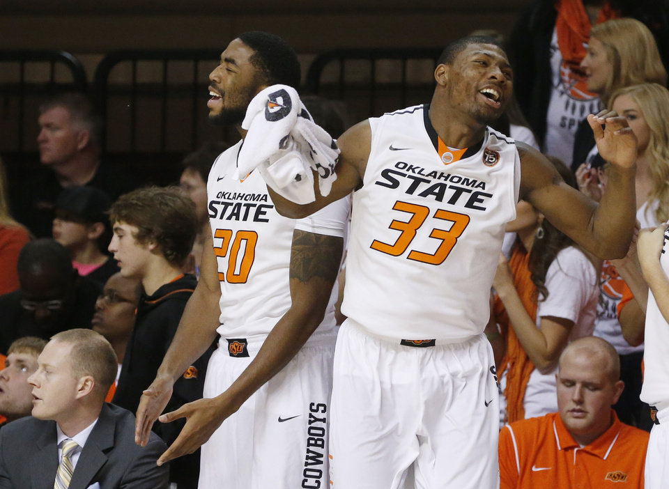 Photo - Oklahoma State post Michael Cobbins (20) and guard Marcus Smart (33) react to a basket by teammate Markel Brown in the first half of an NCAA college basketball game against Mississippi Valley State in Stillwater, Okla., Friday, Nov. 8, 2013. (AP Photo/Sue Ogrocki)