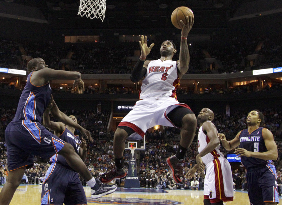 Photo - Miami Heat's LeBron James (6) drives to the basket past Charlotte Bobcats' Gerald Henderson (9) and DeSagana Diop (2) during the first half of an NBA basketball game in Charlotte, N.C., Wednesday, Dec. 26, 2012. (AP Photo/Chuck Burton)