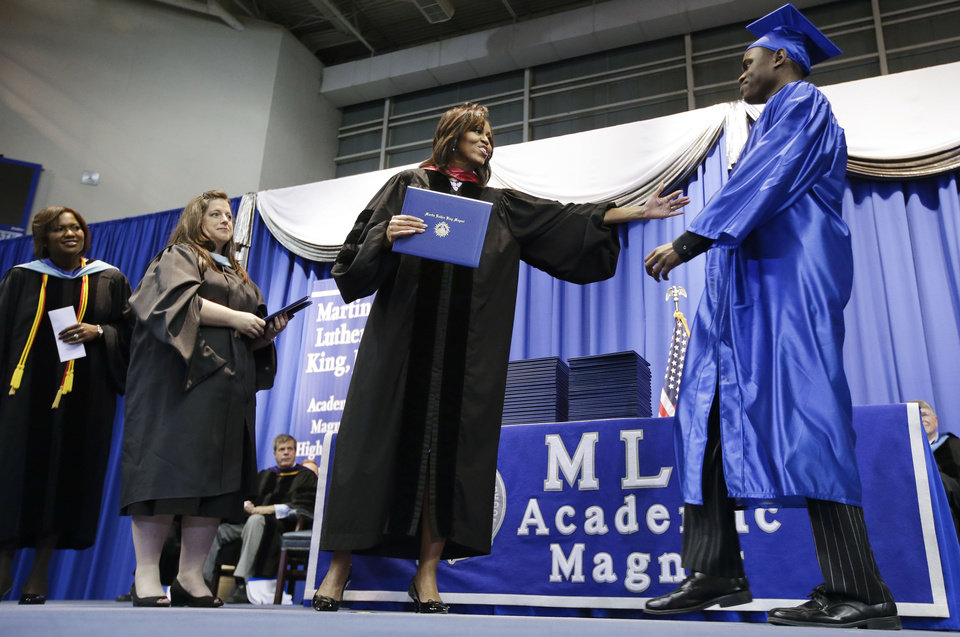 Photo - First lady Michelle Obama, second from right, hands out diplomas at the graduation ceremony for Martin Luther King, Jr. Academic Magnet High School on Saturday, May 18, 2013, in Nashville, Tenn. (AP Photo/Mark Humphrey)