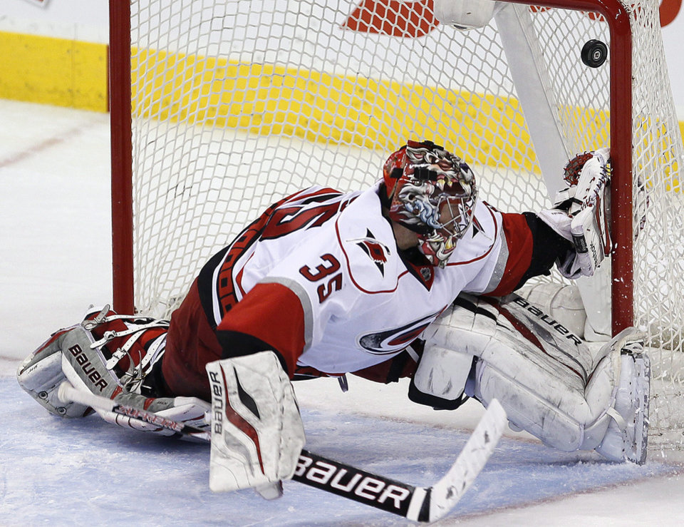 Photo - Carolina Hurricanes goaltender Justin Peters (35) cannot stop a shot from Winnipeg Jets' Paul Postma during the second period of their NHL hockey game in Winnipeg, Manitoba, Thursday, April 18, 2013. (AP Photo/The Canadian Press, John Woods)