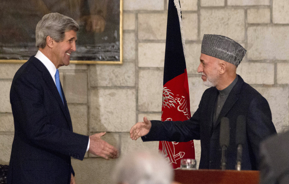 Photo - Secretary of State John Kerry reaches to shakes hands with Afghan President Hamid Karzai at the end of their joint news conference at the Presidential Palace in Kabul, Monday, March 25, 2013. Kerry and Karzai made a show of unity Monday, shortly after the U.S. military ceded control of its last detention facility in Afghanistan, ending a longstanding irritant in relations between the two countries. Kerry, in Afghanistan for an unannounced visit, said he and Karzai were