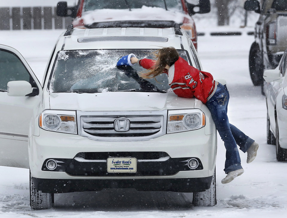 Photo - A girl jumps onto the hood of her car to be able to reach the center of the windshield as she scrapes ice from the glass after Sunday services at Cornerstone Church in Midwest City. Snow began falling in central Oklahoma around 7 Sunday morning, Feb. 2, 2014.   Photo by Jim Beckel, The Oklahoman