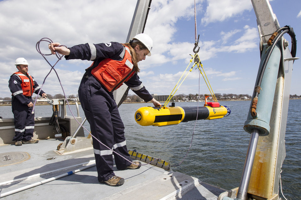 Photo - A submarine built by Bluefin Robotics is lowered into the water by systems engineer Cheryl Mierzwa in Quincy, Mass., Wednesday, April 9, 2014. Bluefin Robotics shipped a version of their submarine to help locate the missing Malaysian Airlines Flight 370, by using its side-scan sonar. (AP Photo/Scott Eisen)