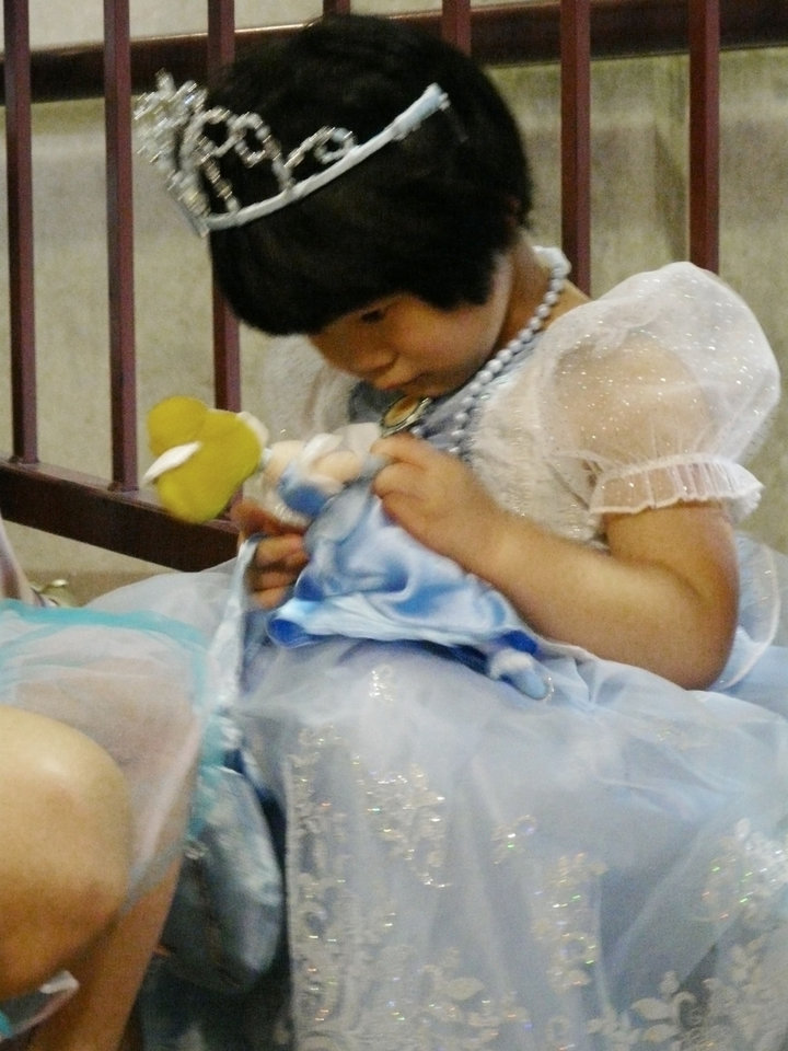 Photo - Li-ying Norlin, 4, dressed as Cinderella, checks out her Cinderella doll while waiting for the children's costume parade to begin Sunday at Catlett Music Center in Norman. PHOTO BY CONNIE HEFNER, FOR THE OKLAHOMAN  Connie Hefner