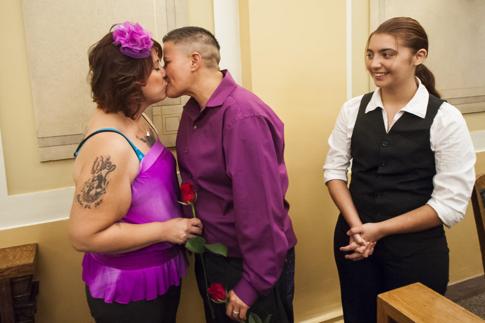 Photo - Jamie, left, and Bea Gallegos kiss after saying their vows while their adopted daughter Whitney Gomez, 15, stands near at the Pueblo County Courthouse in Pueblo, Colo., Friday, July 11, 2014. Technically, their state still does not recognize gay marriages. But that hasn't stopped hundreds of gay Coloradans from getting marriage licenses from two county clerks who argue they still have the legal right to provide them to loving couples. (AP Photo/The Colorado Springs Gazette, Julia Moss)