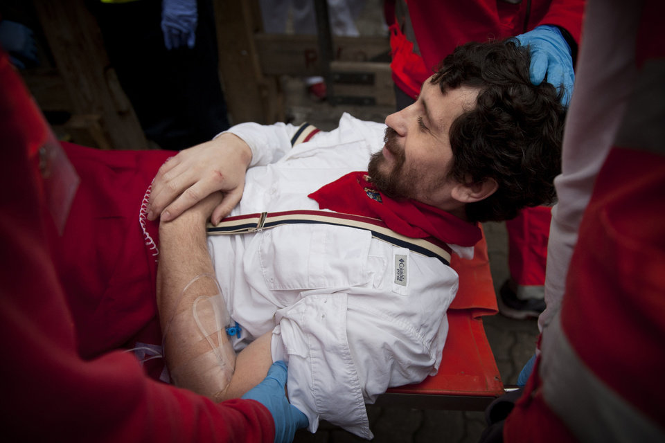 Photo - U.S. runner Bill Hillmann, 35, from Chicago, Ill. is carried on a stretcher after being gored on his right leg by a Victoriano del Rio ranch fighting bull during the running of the bulls of the San Fermin festival, in Pamplona, Spain, Wednesday, July 9, 2014. Journalist and author Hillmann is a veteran San Fermin runner and has written many pieces about the festival. The injury was said to be serious but his life was not in any danger. Revelers from around the world arrive in Pamplona every year to take part on some of the eight days of the running of the bulls glorified by Ernest Hemingway's 1926 novel