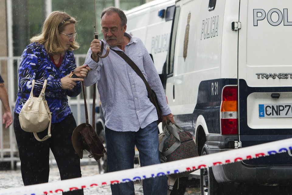 Photo - Relatives of the train crash victims collect the luggage that was under police custody in Santiago de Compostela, Spain, Sunday, July 28, 2013. The driver of a Spanish train that derailed at high speed was being questioned by a judge on Sunday as officials tried to determine if he was responsible for the accident, which killed 79 people. Francisco Jose Garzon Amo, 52, has been held by police on suspicion of reckless homicide. (AP Photo/Lalo R. Villar)