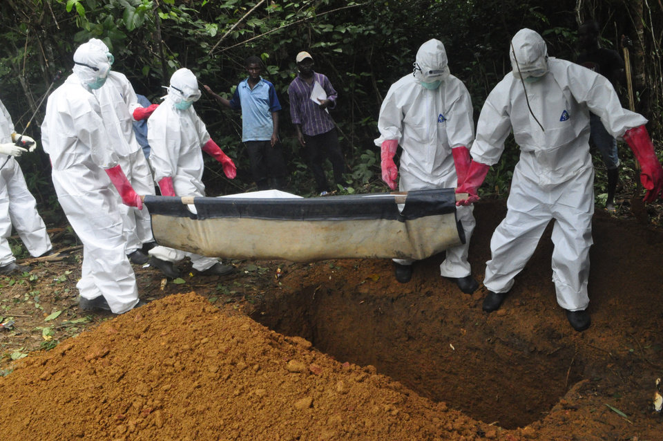 Photo - FILE : In this Saturday, Oct. 18, file photo a burial team in protective gear bury the body of a woman suspected to have died from Ebola virus in Monrovia, Liberia. The disease has ravaged a small part of Africa, but the international image of the whole continent is increasingly under siege, reinforcing some old stereotypes. (AP Photo/Abbas Dulleh, File)