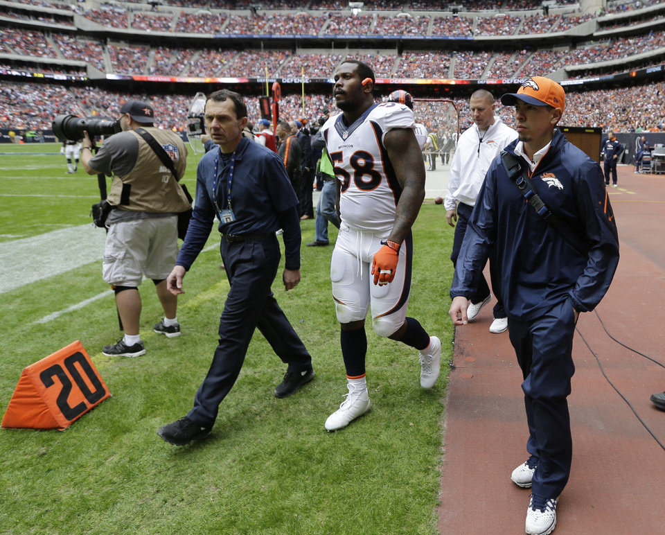 Denver Broncos' Von Miller (58) is walks off the field after he was injured during the first quarter of an NFL football game against the Houston Texans, Sunday, Dec. 22, 2013, in Houston. (AP Photo/David J. Phillip)