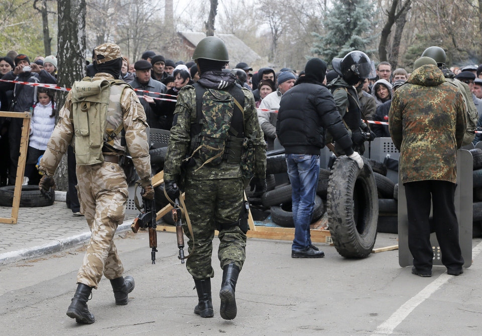 Photo - Armed pro-Russian activists occupy the police station in the eastern Ukrainian town of Slovyansk carrying riot shields on Saturday, April 12, 2014. Pro-Moscow protesters have seized a number of government buildings in the east over the past week, undermining the authority of the interim government in the capital, Kiev. (AP Photo/Efrem Lukatsky)