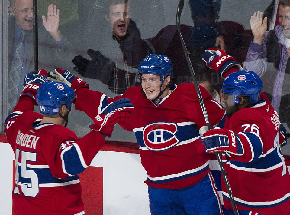Photo - Montreal Canadiens' Brendan Gallagher, center, celebrates with teammates P.K. Subban, right, and Mike Blunden after scoring against the Edmonton Oilers during the first period of an NHL hockey game in Montreal, Tuesday, Oct. 22, 2013. (AP Photo/The Canadian Press, Graham Hughes)