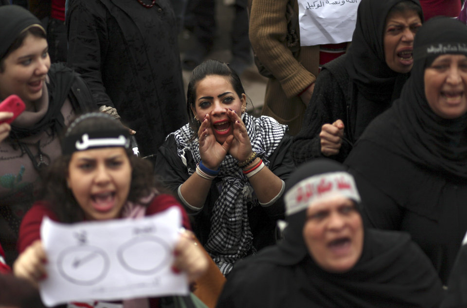 Egyptian protesters chant slogans as they attend a demonstration in Tahrir square in Cairo, Egypt, Friday, Dec. 14, 2012. Opposing sides in Egypt\'s political crisis were staging rival rallies on Friday, the final day before voting starts on a contentious draft constitution that has plunged the country into turmoil and deeply divided the nation.(AP Photo/Khalil Hamra) ORG XMIT: KH104