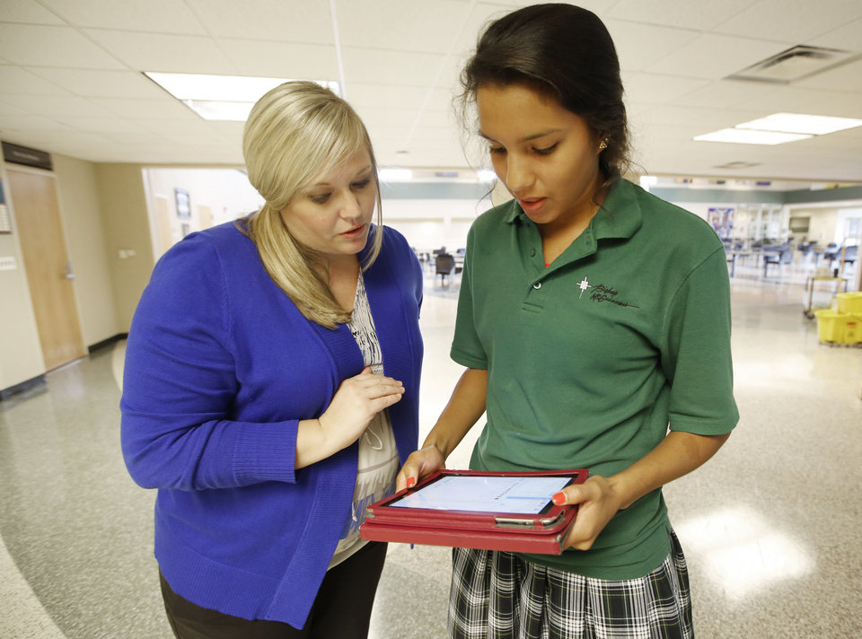 Photo -  Rebekah Hightower, left, director of instructional technology at Bishop McGuinness Catholic High School in Oklahoma City, answers a question for junior student Anne Marie Engel about her iPad. McGuinness issued iPads to all its students this year. Photo By Steve Gooch, The Oklahoman   Steve Gooch -  The Oklahoman