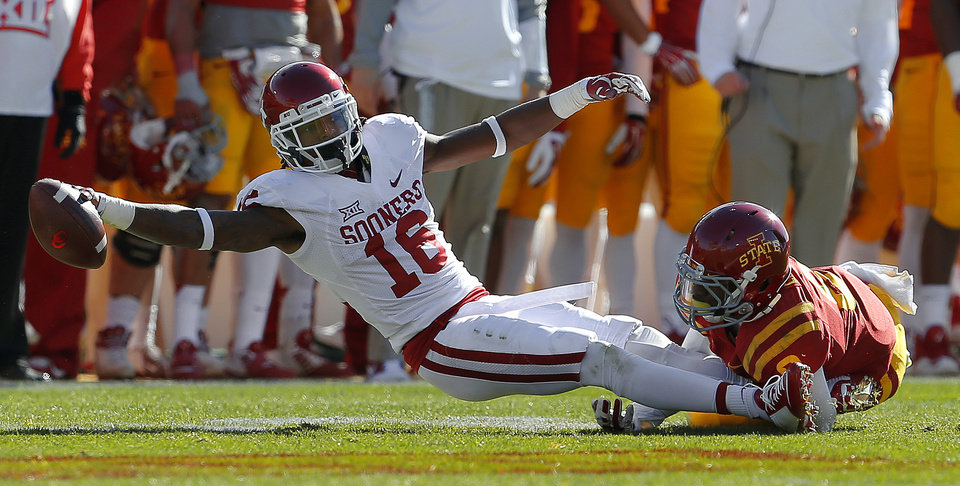Photo - Oklahoma's Michiah Quick (16) reaches for more yards in front of Iowa State's Kenneth Lynn (8) during a college football game between the University of Oklahoma Sooners (OU) and the Iowa State Cyclones (ISU) at Jack Trice Stadium in Ames, Iowa, Saturday, Nov. 1, 2014. Photo by Bryan Terry, The Oklahoman