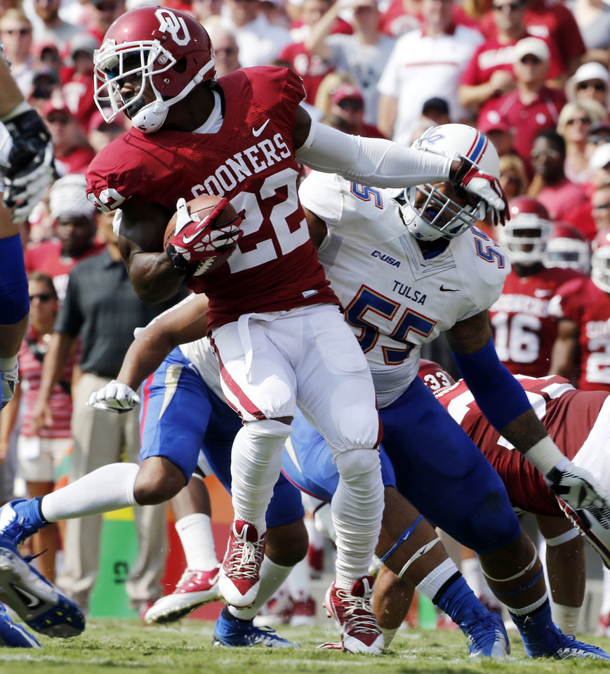 Photo - Oklahoma's Roy Finch (22) spins on a run during a college football game between the University of Oklahoma Sooners (OU) and the Tulsa Golden Hurricane (TU) at Gaylord Family-Oklahoma Memorial Stadium in Norman, Okla., on Saturday, Sept. 14, 2013. Photo by Steve Sisney, The Oklahoman