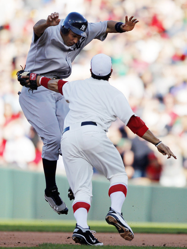 Boston Red Sox\'s Mike Aviles, right, tags out New York Yankees\' Raul Ibanez in a rundown in the eighth inning of a baseball game in Boston, Friday, April 20, 2012. (AP Photo/Michael Dwyer)