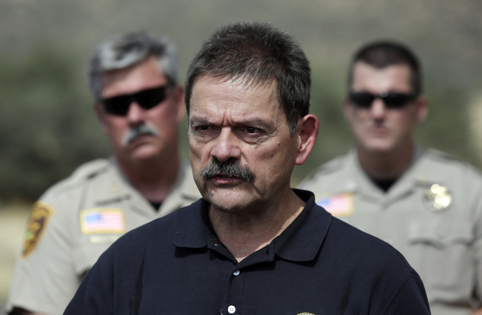 Photo - Mike Dudley, an investigator with the U.S. Forest Service, speaks to reporters after he arrived in Yarnell, Ariz., to being an investigation into the deaths of 19 firefighters, Wednesday, July 3, 2013. An elite crew of firefighters was overtaken by the out-of-control blaze on Sunday, killing 19 members of the crew. (AP Photo/Chris Carlson)