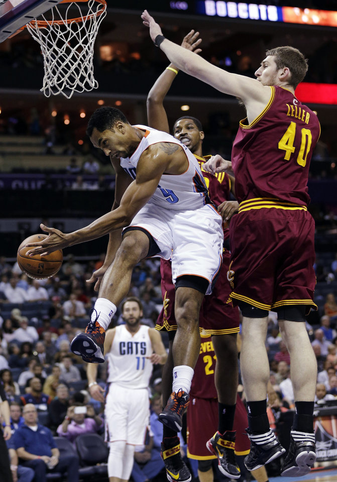 Photo - Charlotte Bobcats' Gerald Henderson (9) passes the ball as he is trapped by Cleveland Cavaliers' Tyler Zeller (40) and Tristan Thompson during the first half of an NBA basketball game in Charlotte, N.C., Wednesday, April 17, 2013. (AP Photo/Chuck Burton)